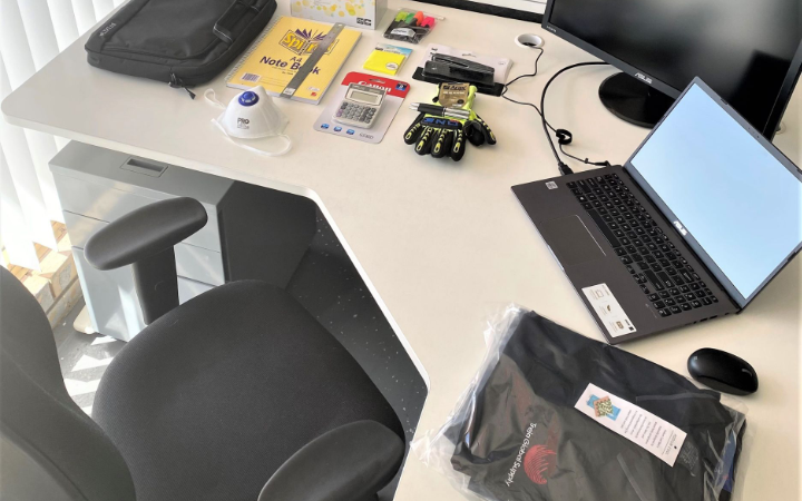 treja desk with safety mask, gloves, shirt and laptop