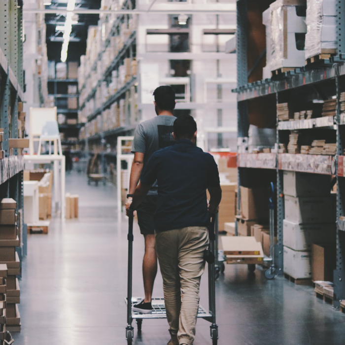 two people wheeling a cart through a warehouse