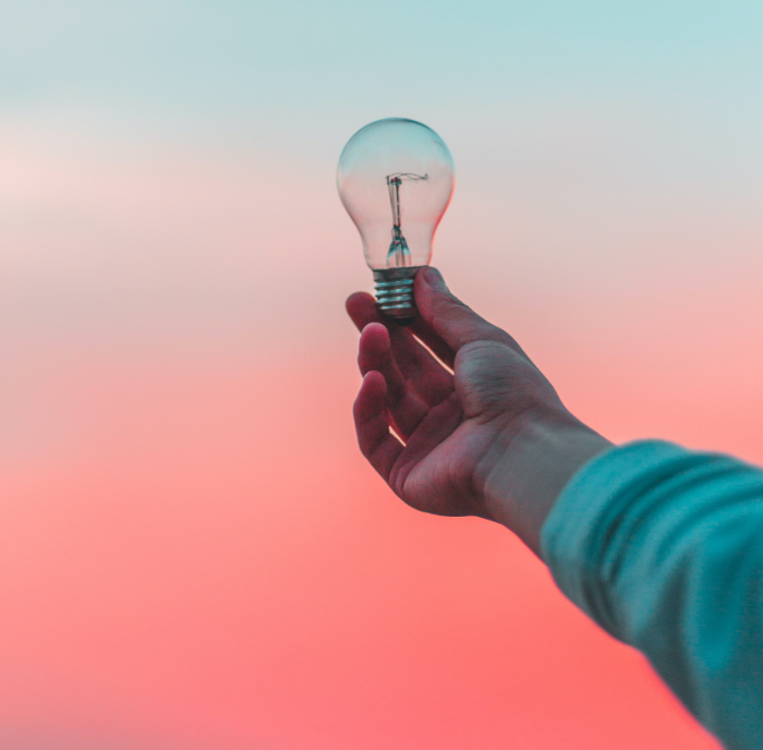 person holding lightbulb up to a pink sky