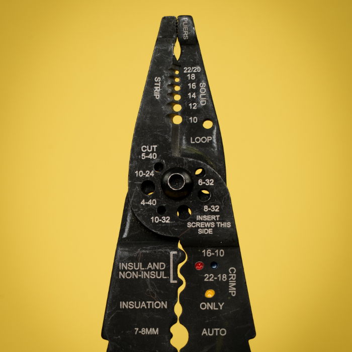 electricians pliers on a yellow background