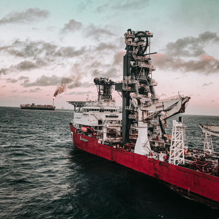 red freighter with oil and gas machinery on the ocean