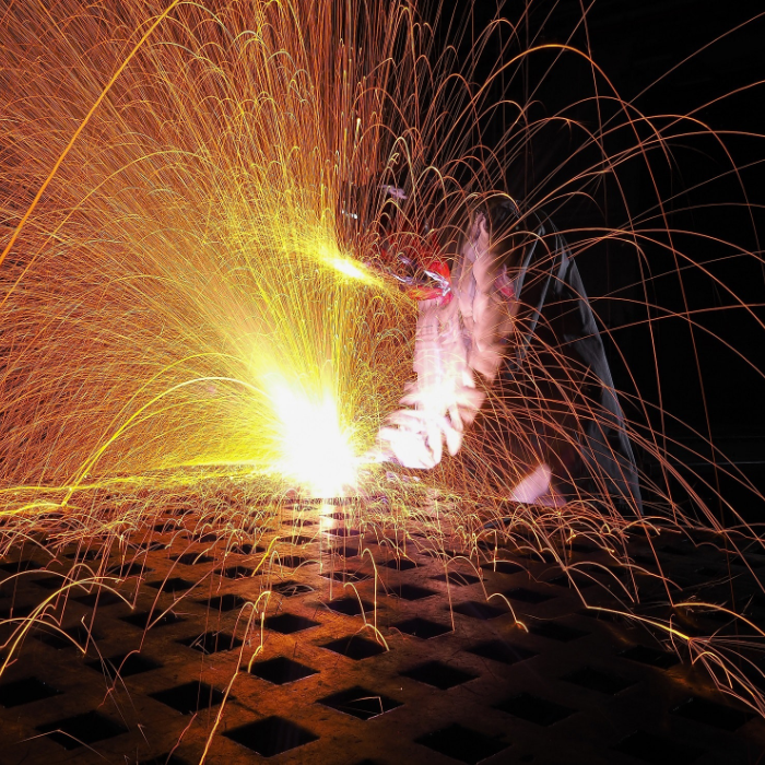 man welding steel frame with safety mask